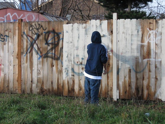 Graffiti Removal - boy painting fence