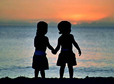 silhouette of boy and girl holding hands on beach at sunset