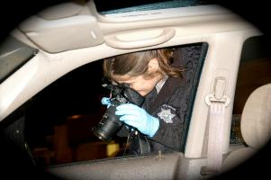 A Criminalist photographs a vehicle at a crime scene