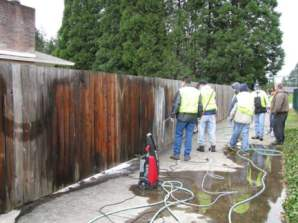 Washington County Jail inmate workers cleaning graffiti from a fence