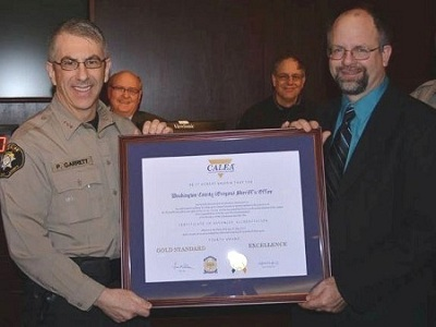 Sheriff Garrett receiving recognition by the Board of Commissioners for CALEA accreditation
